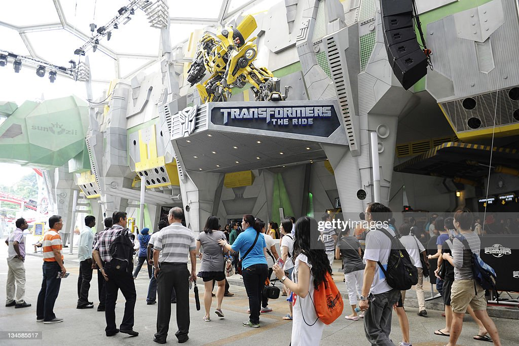 Visitors queue for the Transformers-themed amusement park ride at Universal Studios Singapore on its launch day on December 3, 2011. 'Transformers: The Ride' is based on the Transformers movie franchise directed by Michael Bay.