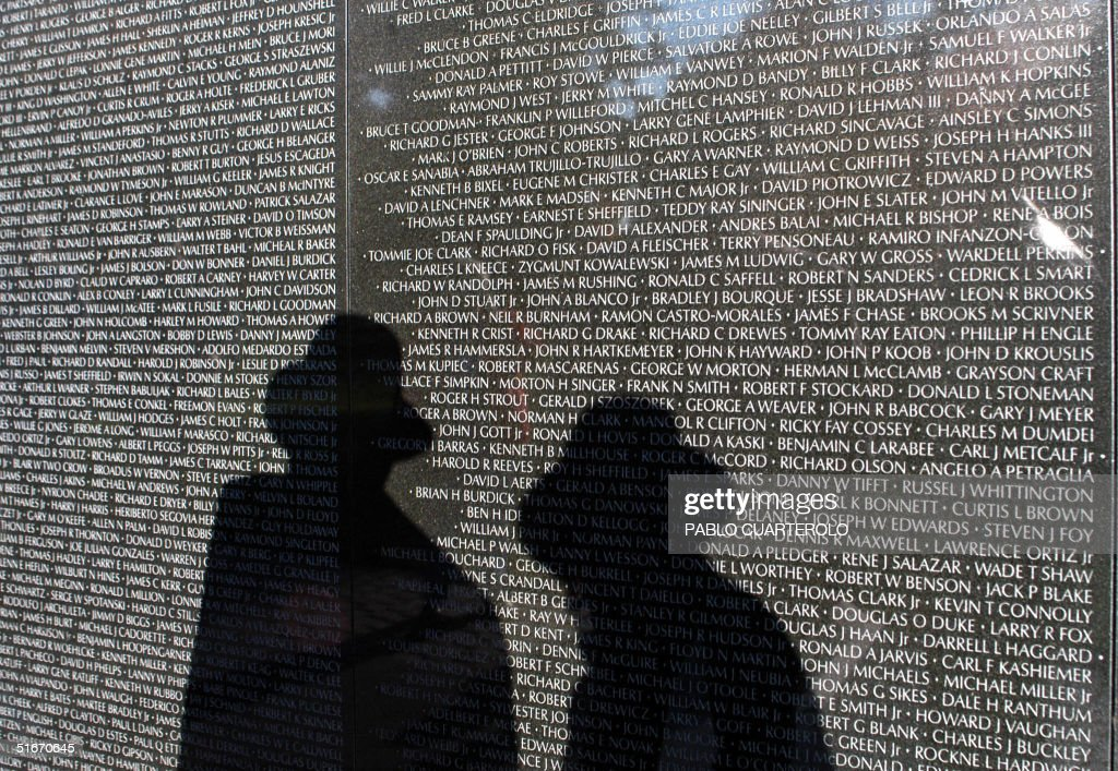 Visitors read the names on the Vietnam Veterans Memorial on the National Mall in Washington DC, 08 November 2002, during events commemorating Veterans Day, which will be observed Monday, 11 November 2002.