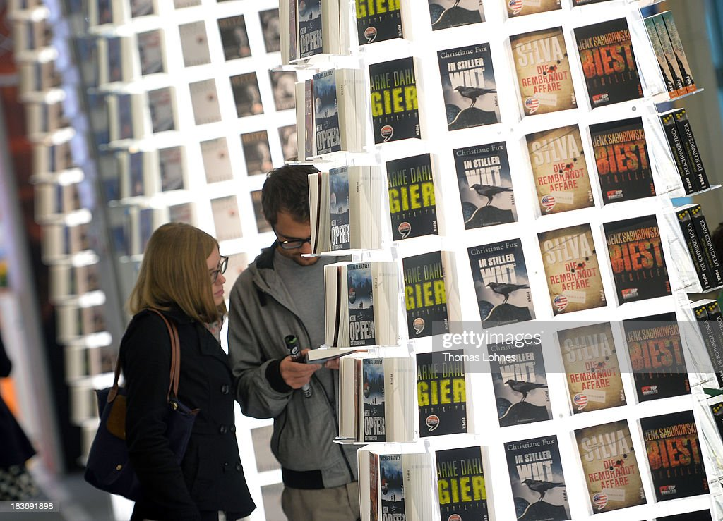 Visitors reading in a book at the 2013 Frankfurt Book Fair on October 9, 2013 in Frankfurt, Germany. This year's fair will be open to the public from October 9-13 and the official partner nation is Brazil.