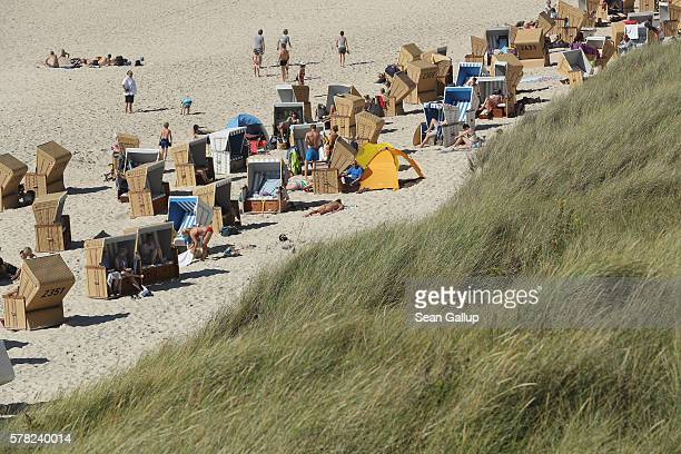 Visitors relax among beach chairs next to dunes at a beach on Sylt Island on July 19 2016 near Wenningstedt Germany Sylt Island with its long...