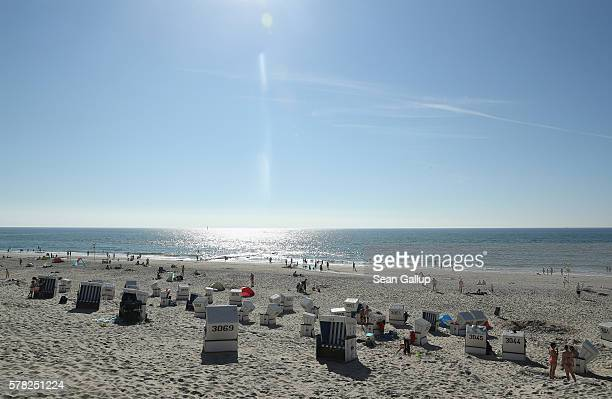 Visitors relax among beach chairs on a beach on Sylt Island on July 19 2016 near Wenningstedt Germany Sylt Island with its long stretches of sand...