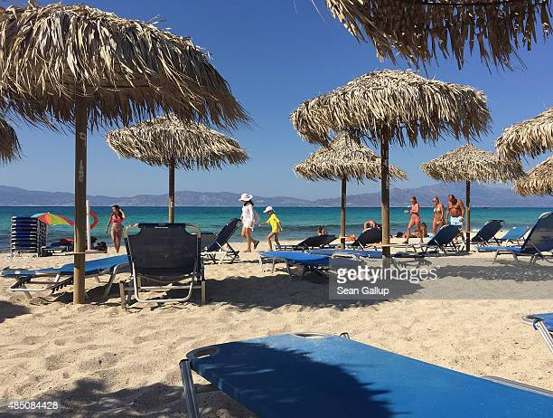 Visitors relax among beach chairs on the sandy northern beach on Chrissi Islet as the southeastern coast of Crete is visible behind on August 22 2015...