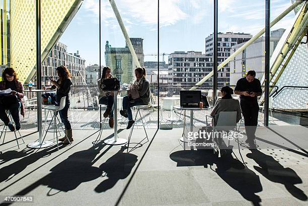 Visitors relax and check their mobile phones at tables in a rest room at the Barcelona Growth Center in Barcelona Spain on Thursday Feb 20 2014 A...