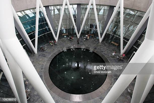 Visitors relax around the rain oculus in the main atrium of the ArtScience Museum on February 19 2011 at Marina Bay Sands Singapore The ArtScience...