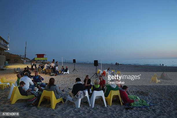 Visitors relax at an outdoor cafe at a beach after sunset on Sylt Island on July 19 2016 near Wenningstedt Germany Sylt Island with its long...
