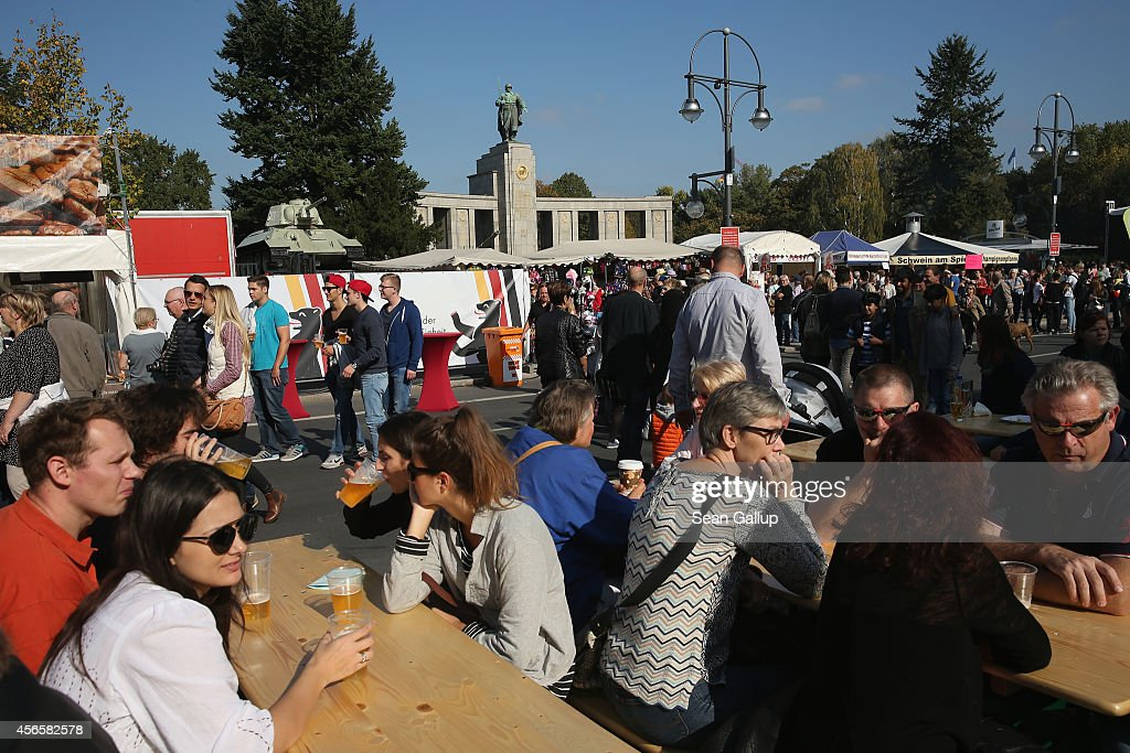 Visitors relax at beer tables near the Soviet monument to the liberation of Berlin from the Nazis by the Soviet Army in 1945 in Tiergarten Park on German Unity Day (Tag der Deutschen Einheit) on October 3, 2014 in Berlin, Germany. Germany is celebrating the 24th anniversary of the day when former West Germany and East Germany reunited into modern Germany in 1990 following the end of the Cold War. This year Germany will also celebrate the 25th anniversary of the fall of the Berlin Wall that heralded the collapse of communist authority in East Germany.