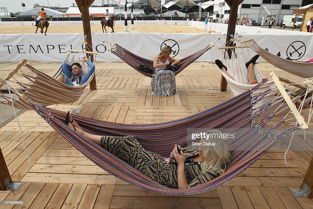 Visitors relax next to the Tom Tailor polo field at the 2012 Bread & Butter fashion trade fair at former Tempelhof Airport on July 6, 2012 in Berlin, Germany. Bread & Butter is the world's largest trade fair for street fashion.
