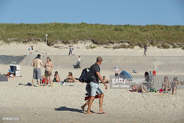 Visitors relax on a beach on Sylt Island on July 19 2016 near Wenningstedt Germany Sylt Island with its long stretches of sand beaches and its...