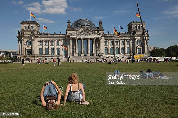 Visitors relax on a sunny day on grass in front of the Reichstag on August 22 2011 in Berlin Germany Germany which has thus far endured a summer...