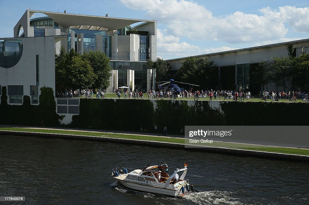 Visitors relax on the back lawn during the annual open-house day at the Chancellery as a boat motors past on the Spree river on August 25, 2013 in Berlin, Germany. Approximately 150,000 visitors took advantage of the annual event held at the Chancellery and German government ministries to get an inside glimpse.