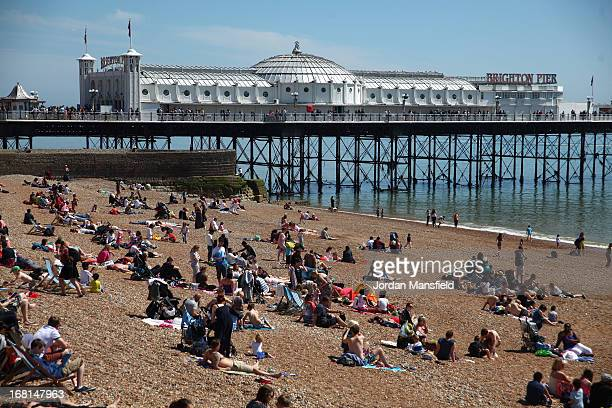 Visitors relax on the beach in front of Brighton Pier on May 6 2013 in Brighton England Visitors have flocked to Brighton Beach as the Met Office...