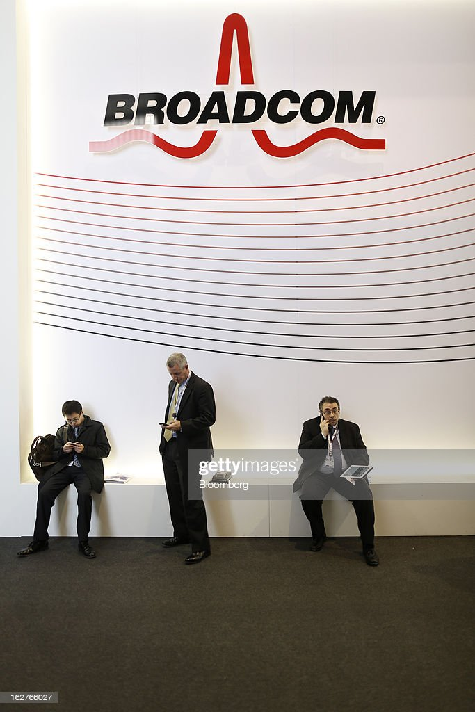 Visitors rest and check their mobile devices outside the Broadcom Corp. pavilion at the Mobile World Congress in Barcelona, Spain, on Tuesday, Feb. 26, 2013. The Mobile World Congress, where 1,500 exhibitors converge to discuss the future of wireless communication, is a global showcase for the mobile technology industry and runs from Feb. 25 through Feb. 28. Photographer: Simon Dawson/Bloomberg via Getty Images