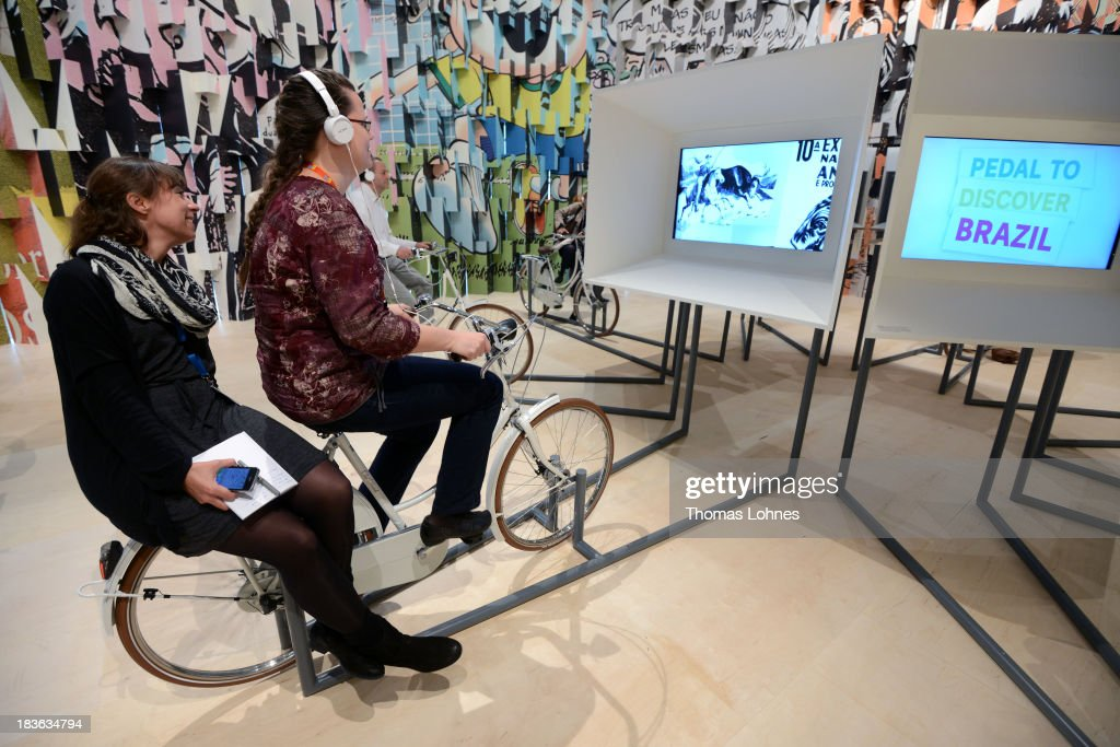 Visitors ride a bicycle for a multimedia show at the exhibition of Guest of Honour Brazil a day before the launch of the 2013 Frankfurt Book Fair on October 8, 2013 in Frankfurt, Germany. This year's fair will be open to the public from October 9-13 and the official partner nation is Brazil.