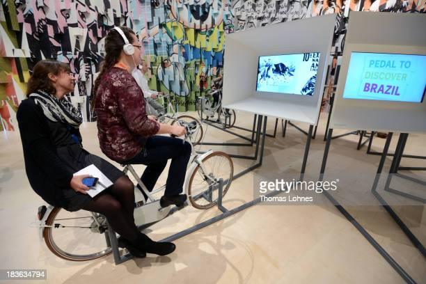 Visitors ride a bicycle for a multimedia show at the exhibition of Guest of Honour Brazil a day before the launch of the 2013 Frankfurt Book Fair on...