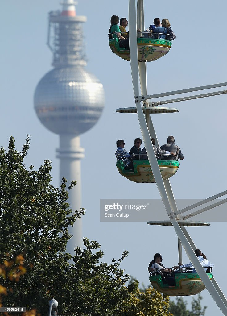 Visitors ride a ferris wheel as the broadcast tower at Alexanderplatz stands behind on German Unity Day (Tag der Deutschen Einheit) on October 3, 2014 in Berlin, Germany. Germany is celebrating the 24th anniversary of the day when former West Germany and East Germany reunited into modern Germany in 1990 following the end of the Cold War. This year Germany will also celebrate the 25th anniversary of the fall of the Berlin Wall that heralded the collapse of communist authority in East Germany.