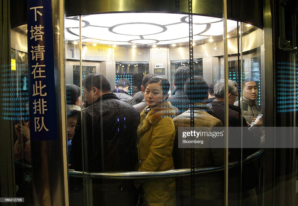 Visitors ride in a glass elevator inside the Oriental Pearl Tower in the Pudong area of Shanghai, China, on Wednesday, Jan. 30, 2013. China's economic growth accelerated for the first time in two years as government efforts to revive demand drove a rebound in industrial output, retail sales and the housing market. Photographer: Tomohiro Ohsumi/Bloomberg via Getty Images