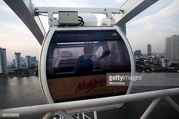 Visitors ride in a passenger pod of a ferris wheel displaying advertising for Mekhong Distillery Ltd at Asiatique The Riverfront openair mall in...