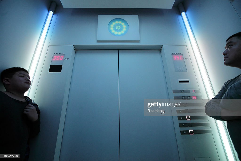 Visitors ride in an elevator inside the Shanghai World Financial Center in the Pudong area of Shanghai, China, on Wednesday, Jan. 30, 2013. China's economic growth accelerated for the first time in two years as government efforts to revive demand drove a rebound in industrial output, retail sales and the housing market.Photographer: Tomohiro Ohsumi/Bloomberg via Getty Images