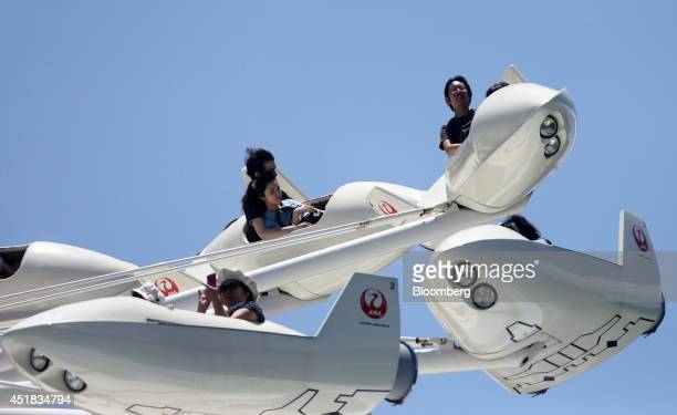 Visitors ride on the Star Jets at Tokyo Disneyland operated by Oriental Land Co in Urayasu Chiba Prefecture Japan on Tuesday July 8 2014 Oriental...