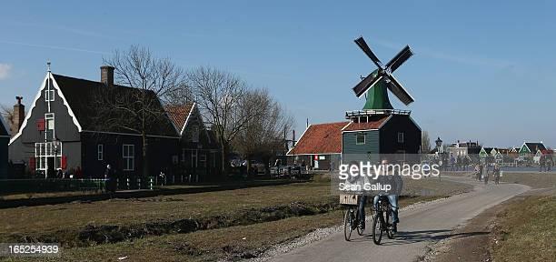Visitors ride past traditional houses and a windmill at the Zaanse Schans outdoor mueseum on April 1 2013 in Zaandijk Netherlands Zaanse Schans...