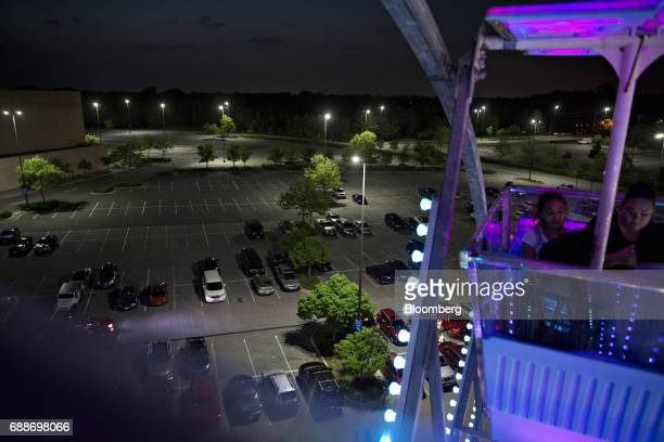 Visitors ride the Dream Wheel during the Dreamland Amusements carnival in the parking lot of the Marley Station Mall in Glen Burnie Maryland US on...