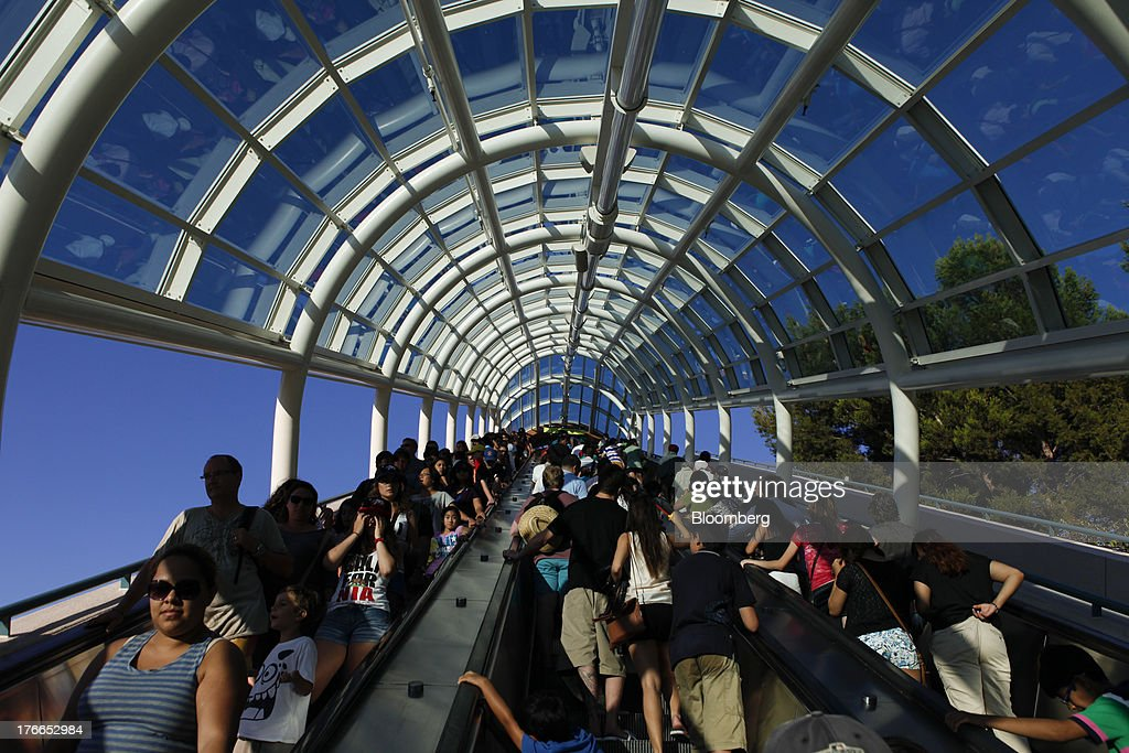 Visitors ride the Starway escalator at the Universal Studios Hollywood theme park in Hollywood, California, U.S., on Thursday, Aug. 15, 2013. NBC Universal, majority owned by Comcast Corp., operates some of the most-watched U.S. cable TV channels, in addition to its flagship broadcast network, a film studio and the Universal Studios amusement parks. Photographer: Patrick T. Fallon/Bloomberg via Getty Images