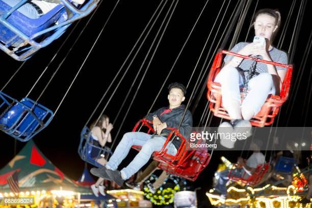 Visitors ride the Tornado swing during the Dreamland Amusements carnival in the parking lot of the Marley Station Mall in Glen Burnie Maryland US on...