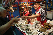 Visitors sample French saucisson or cured sausage from Alsace at the International Green Week agricultural trade fair on January 16 2015 in Berlin...