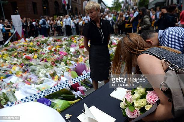 Visitors sign condolences and flowers are laid at a makeshift memorial near the scene of a fatal siege in the heart of Sydney's financial district on...