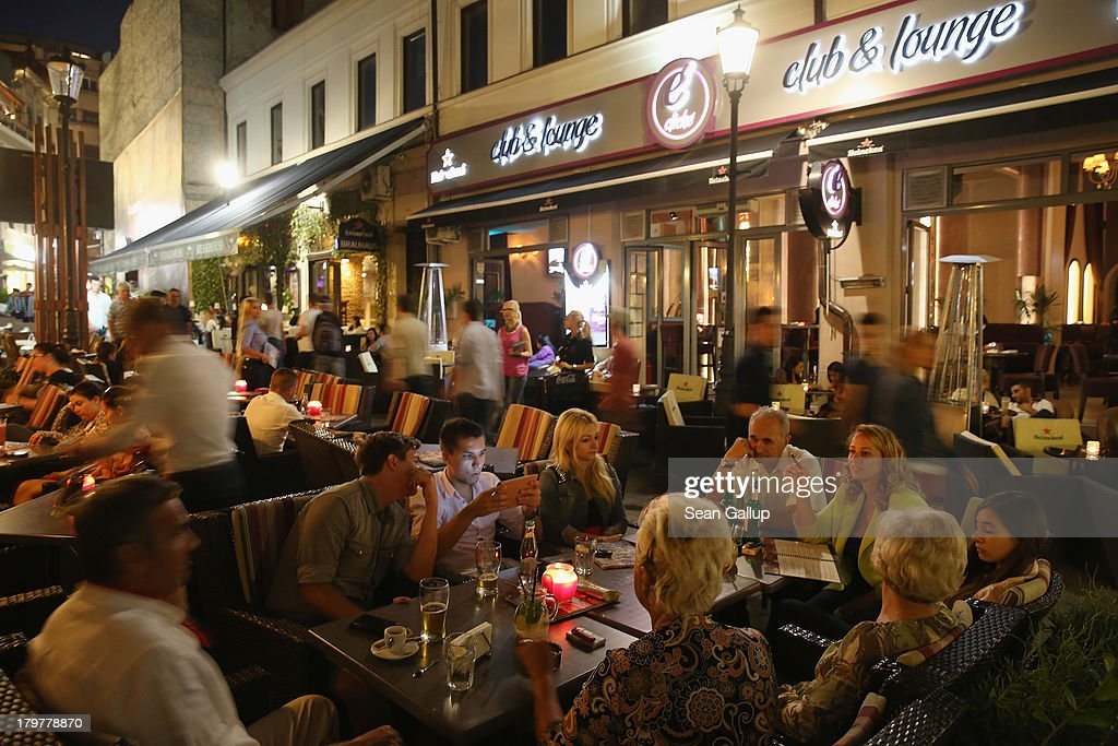 Visitors sit at outdoor restaurants and bars in the Old Town Lipscani district on September 6, 2013 in Bucharest, Romania. While the country's economic output has risen significantly since it joined the European Union in 2007, it still lags in infrastructure development and the fight against corruption.