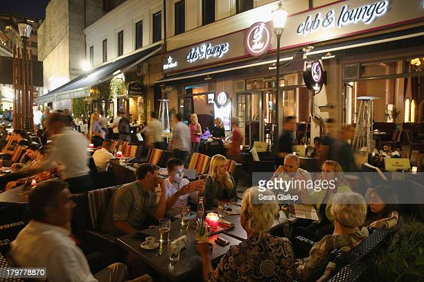 Visitors sit at outdoor restaurants and bars in the Old Town Lipscani district on September 6 2013 in Bucharest Romania While the country's economic...