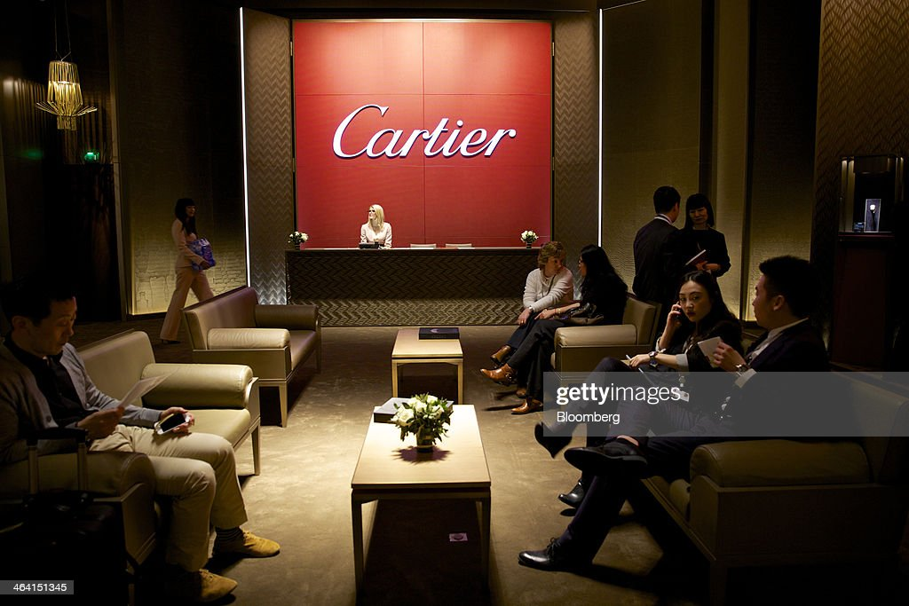 Visitors sit at the Cartier display booth at the Salon International de la Haute Horlogerie (SIHH) watch fair in Geneva, Switzerland, on Monday, Jan. 20, 2014. Enthusiasts coveting $50,000 Cartier watches, a luxury unit of Cie. Financiere Richemont SA, at the Swiss industry's annual fair bumped opening meetings to resolve the three-year-old Syrian civil war out of the lakeside town. Photographer: Gianluca Colla/Bloomberg via Getty Images