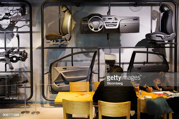 Visitors sit in front of a display of components for the Hyundai Motor Co Sonata sedan at a company dealership in the Gangnam district of Seoul South...
