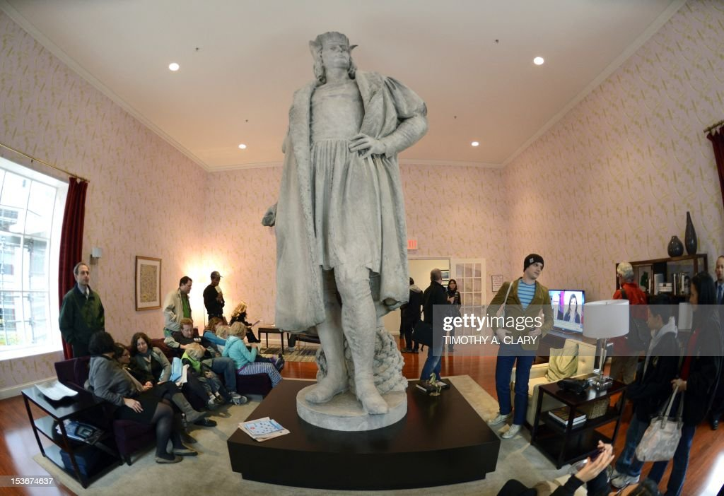 Visitors sit in Japanese artist Tatsu Nishi's installation around the colossal 13-foot-tall statue of Christopher Columbus at Columbus Circle in New York on October 8, 2012 standing in a fully furnished, modern living room featuring tables, chairs, couch, rug, and flat-screen television, reflecting the artist's interpretation of contemporary New York style. His installation around the weathered marble statue, designed by the Italian sculptor Gaetano Russo in 1892, rises to more than 75 feet atop a granite column. Visitors can enter the 'Discovering Columbus' apartment built around the statue elevated from the ground by scaffolding located in the downtown Columbus Circle until November 18. AFP PHOTO/TIMOTHY A. CLARY