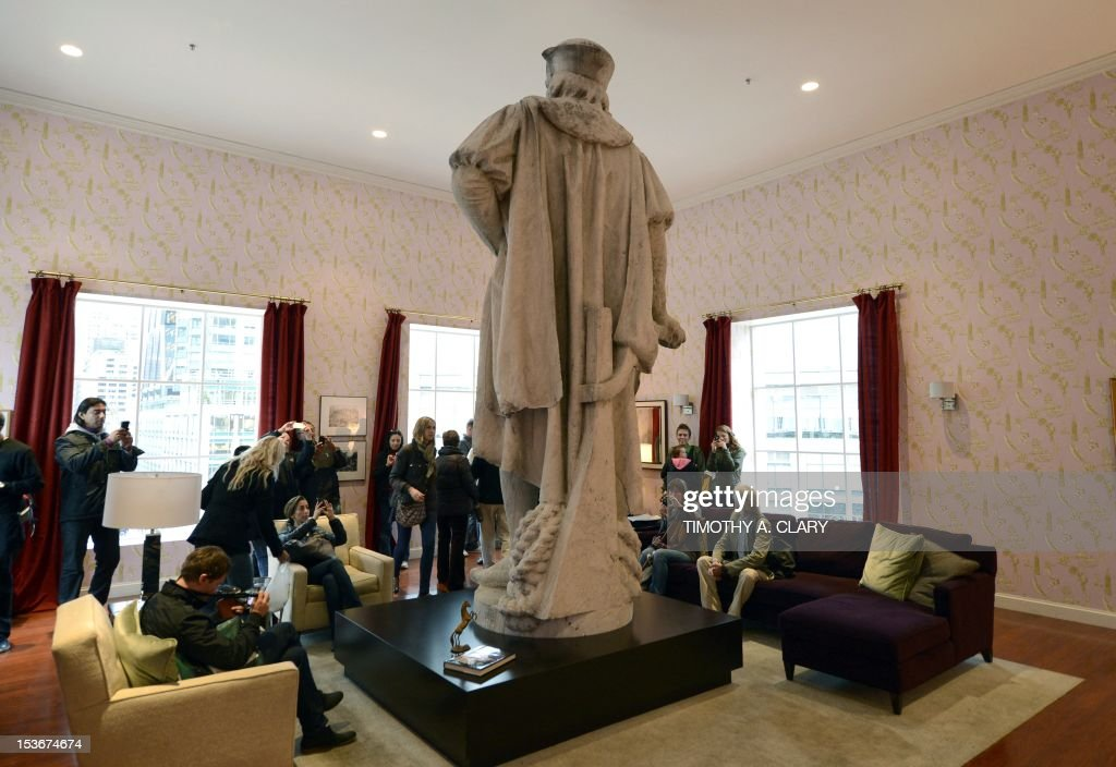 Visitors sit in Japanese artist Tatsu Nishi's installation around the colossal 13-foot-tall statue of Christopher Columbus at Columbus Circle in New York on October 8, 2012 standing in a fully furnished, modern living room featuring tables, chairs, couch, rug, and flat-screen television, reflecting the artist's interpretation of contemporary New York style. His installation around the weathered marble statue, designed by the Italian sculptor Gaetano Russo in 1892, rises to more than 75 feet atop a granite column. Visitors can enter the 'Discovering Columbus' apartment built around the statue elevated from the ground by scaffolding, located in the downtown Columbus Circle until November 18. AFP PHOTO/TIMOTHY A. CLARY