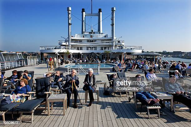 Visitors sit in the sun on the deck of the SS Rotterdam on October 9 2010 The largest passenger ship ever built in the Netherlands is moored in the...