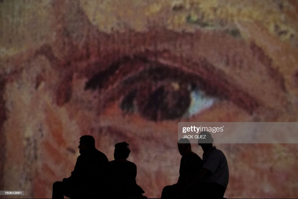 Visitors sit looking at a giant screen featuring an image of the work of Dutch painter Vincent van Gogh during a traveling multimedia art exhibition entitled 'Van Gogh alive' on February 4, 2013 at the Israel Trade Fairs and Convention Center in Tel Aviv. The interactive installation, featuring thousands of 360-degree lifelike images of Van Gogh's works, has already toured Turkey, Singapore and the United States and will take place in Tel Aviv until March 4, 2013. AFP PHOTO / JACK GUEZ