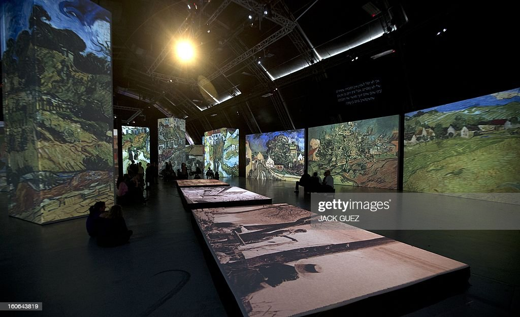 Visitors sit looking at giant screens featuring images of the work of Dutch painter Vincent van Gogh during a traveling multimedia art exhibition entitled 'Van Gogh alive' on February 4, 2013 at the Israel Trade Fairs and Convention Center in Tel Aviv. The interactive installation, featuring thousands of 360-degree lifelike images of Van Gogh's works, has already toured Turkey, Singapore and the United States and will take place in Tel Aviv until March 4, 2013. AFP PHOTO / JACK GUEZ