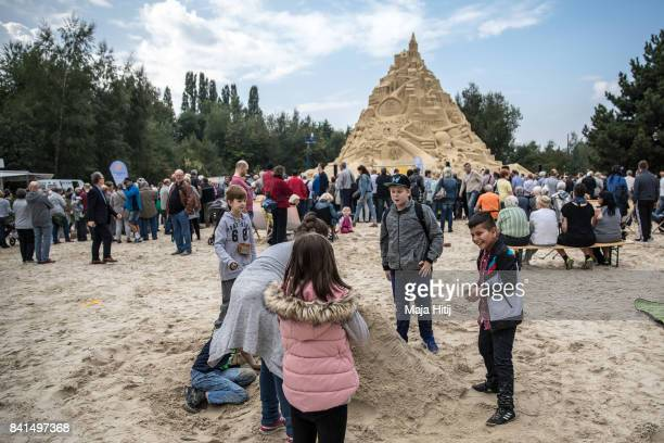 Visitors sit near the Sandburg sandcastle on September 1 2017 in Duisburg Germany A local travel agency commissioned the building of the sandcastle...
