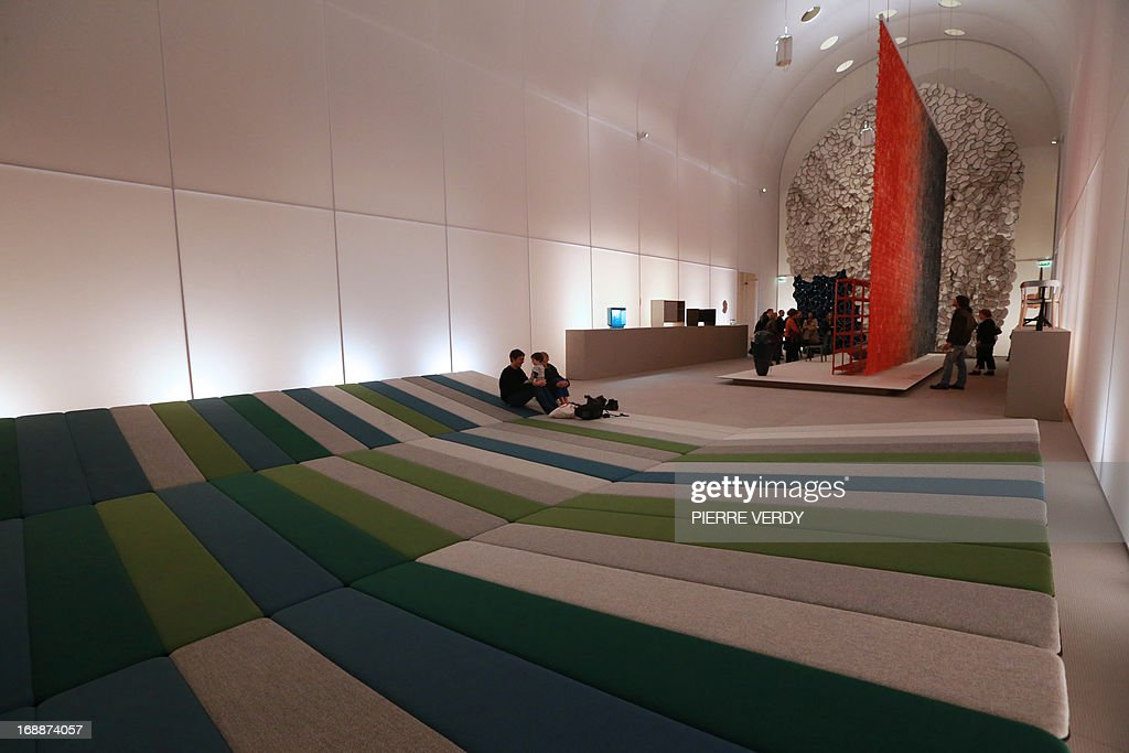 Visitors sit on a 'textile field' at an exhibition covering the work of design team Ronan & Erwan Bouroullec, formed by the two brothers from Brittany, at the Musee des Arts Decoratifs in Paris on May 16, 2013.
