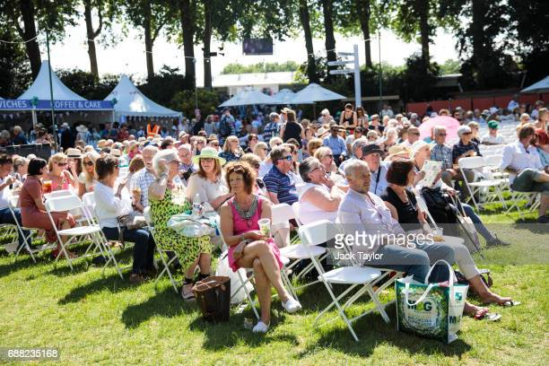 Visitors sit on chairs in the sunshine as a band performs at the Chelsea Flower Show on May 25 2017 in London England Visitors enjoy warm weather and...