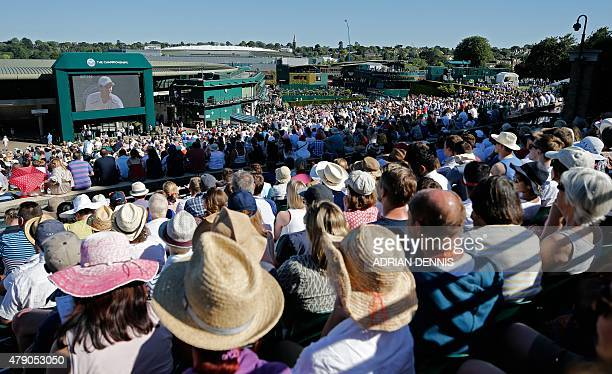 Visitors sit on Murray Mound and watch a giant screen showing Britain's Andy Murray play Kazakhstan's Mikhail Kukushkin on day two of the 2015...