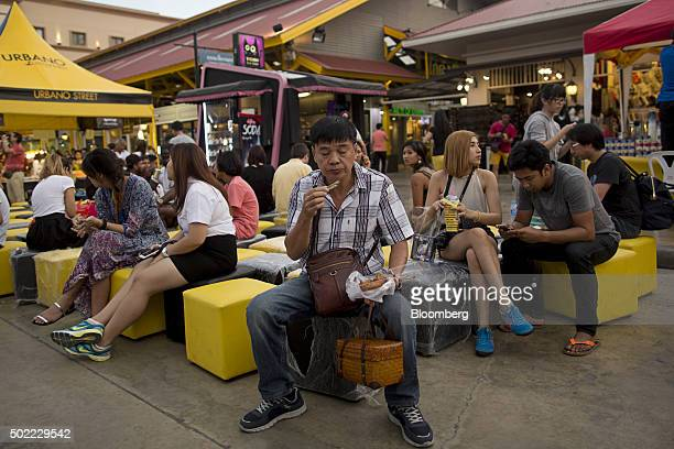 Visitors sit on stools at Asiatique The Riverfront openair mall in Bangkok Thailand on Friday Dec 18 2015 Thai economic indicators have shown signs...