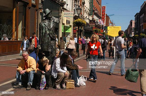 Visitors sit on the base of a statue of Irishman James Joyce author one of Dublin's most famous literary masterpieces 'Ulysses' 15 May 2004 in Dublin...