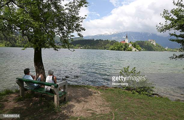 Visitors sit on the shore of Lake Bled and look towards the church of the Assumption of Mary a pilgrimage site and tourist attraction in Bled...
