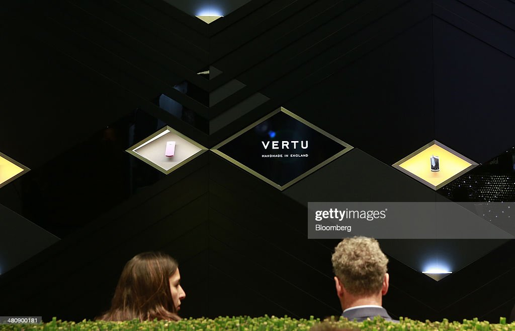 Visitors sit outside the Vertu luxury mobile phone booth, during the Baselworld luxury watch and jewelry fair in Basel, Switzerland, on Thursday, March 27, 2014. Over 1,400 companies from the watch, jewelry and gem industries will display their latest innovations and products to more than 120,000 visitors at this year's luxury show. Photographer: Gianluca Colla/Bloomberg via Getty Images