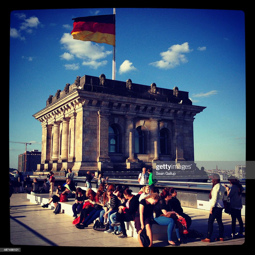 Visitors sit under a German flag on the roof terrace of the Reichstag on April 28, 2014 in Berlin, Germany. The Reichstag, home of the Bundestag, the German parliament, is among the city's major landmarks and a favourite tourist destination.