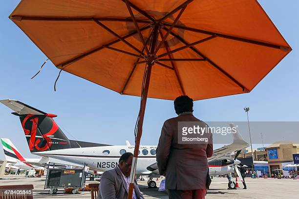 Visitors sit under a parasol and shelter from the sun during the India Aviation 2014 air show held at the Begumpet Airport in Hyderabad India on...