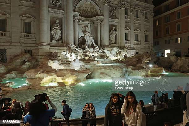 Visitors snap photos of one another in the evening at the Trevi Fountain on October 26 2016 in Rome Italy Rome is among Europe's major tourist...