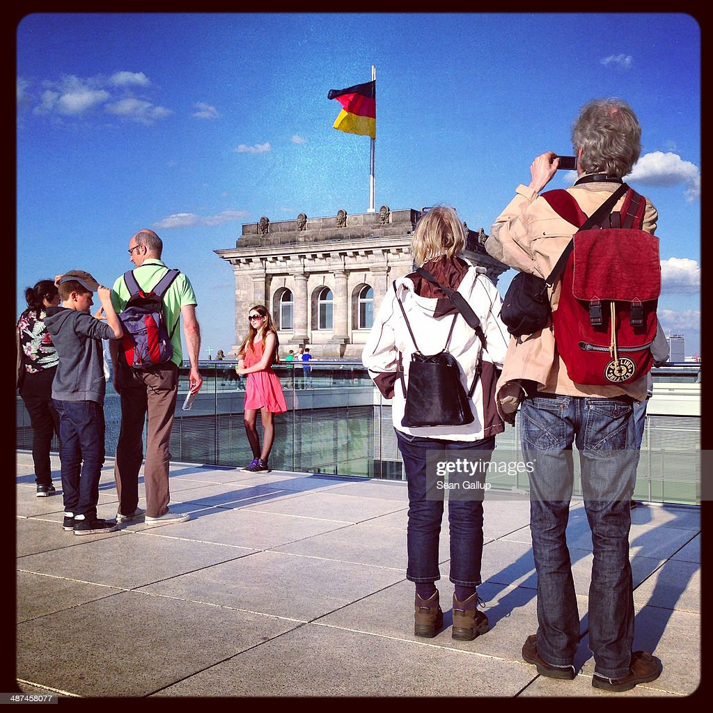 Visitors snap photos on the roof terrace as a German flag flies behind at the Reichstag on April 28, 2014 in Berlin, Germany. The Reichstag, home of the Bundestag, the German parliament, is among the city's major landmarks and a favourite tourist destination.